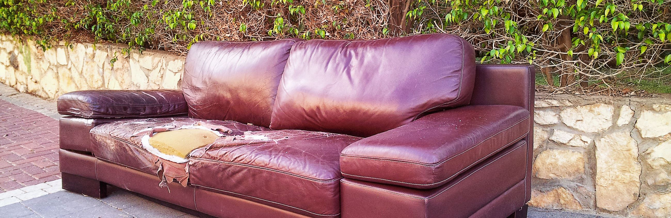 Damaged couch waiting for trash pickup