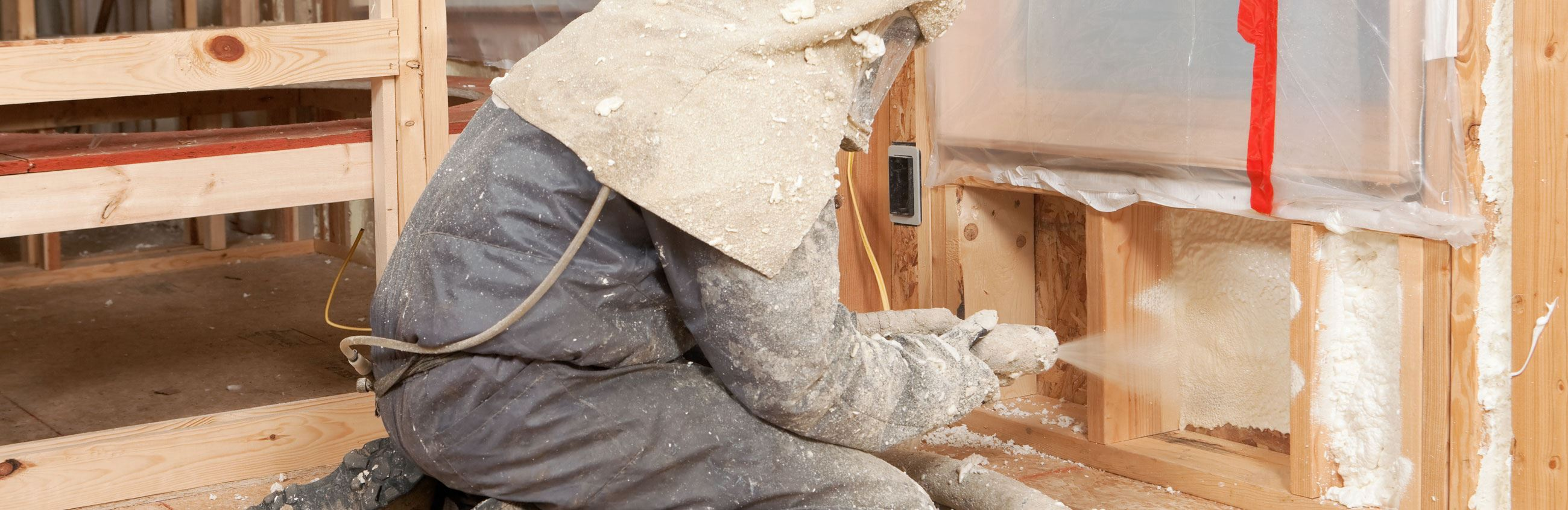 Man in respirator suit spraying insulation